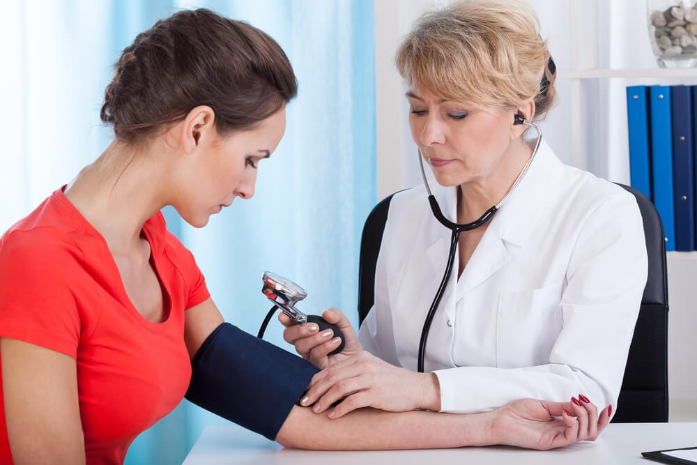 A Transparent Female docter checking the blood pressure of a female patient
