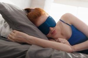 Woman In Bed Sleeping With Sleep Mask On Eyes
