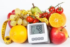 Blood pressure monitor with result of measurement, fruits with vegetables and centimeter