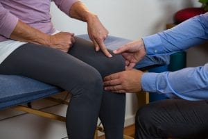Physiotherapist examining a female patients knee