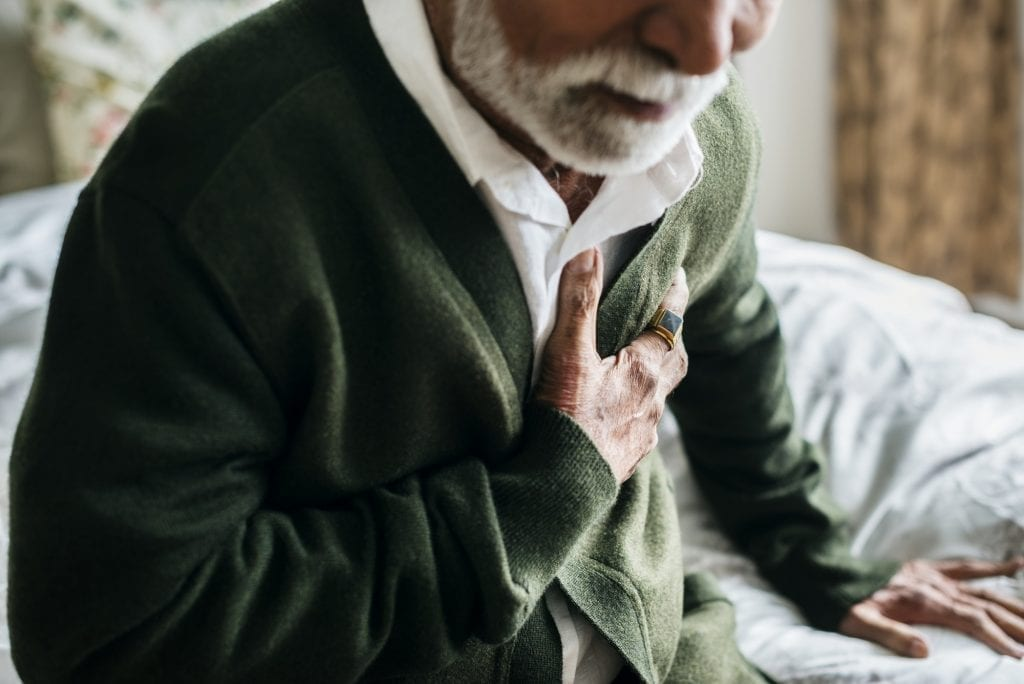 An elderly Indian man with heart problems focused on his heart health.