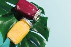Fresh made smoothies in jars on monstera leaf