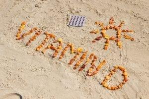 Medical pills, inscription vitamin D and shape of sun at beach