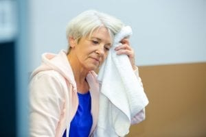 senior woman mopping brow with towel after exercising